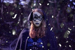 Plus size woman with red hair wearing a purple outfit dressed as a witch and evil queen wearing a mask while it's snowing