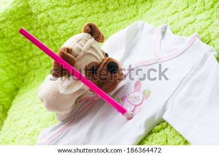 Plush puppy painting little bunny on baby sleepsuits. #186364472