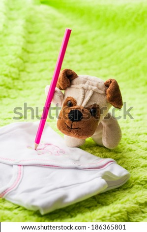 Plush puppy painting little bunny on baby sleepsuits. #186365801