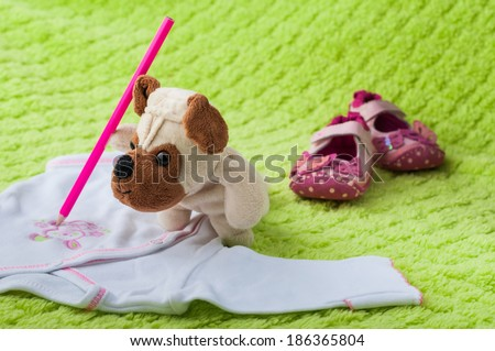 Plush puppy painting little bunny on baby sleepsuits. #186365804