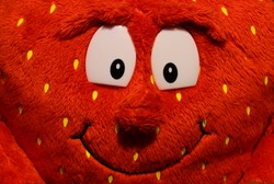 Plush red mascot with a smile and big eyes.