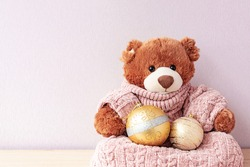 Plush teddy bear in warm knitted clothes sitting by xmas baubles. Stuffed toy and Christmas tree decoration. Soft cuddly plaything for children. Warmth and security, heartwarming family holidays