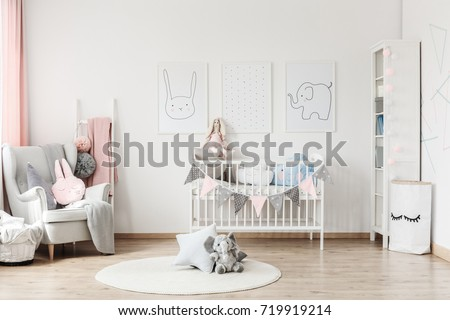 Plush toy and pillow on white round carpet in baby\'s room with grey armchair and posters on wall
