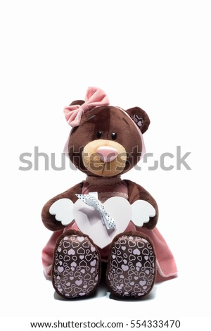 Plush toy bear sitting with heart a pink heart on isolated white background. Valentine day #554333470