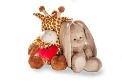 Plush toy giraffe and Bunny rabbit hold a red heart isolated on a white background Colorful plush toy. Colored stuffed toy-giraffe and Bunny. White and brown giraffe, grey rabbit