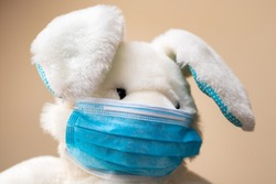 Plush toy rabbit wearing a face mask