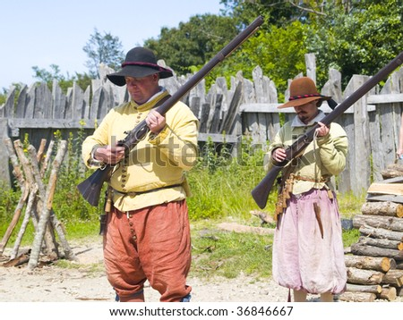 PLYMOUTH, MA - July 24, 2009 - Male pilgrims practice a musket drill at Plimoth Plantation.  The plantation features the recreation of an English village in 1627.