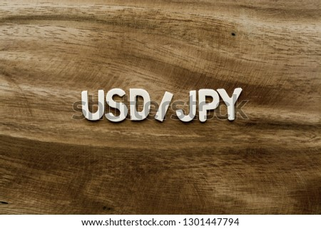 """Plywood alphabets on acacia wooden texture background concept. The word """"USD/JPY (United States Dollar to Japanese Yen)"""" on wood pattern backdrop."""