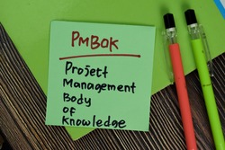 PMBOK - Project Management Body of Knowledge write on sticky notes isolated on Wooden Table. Business of Financial concept