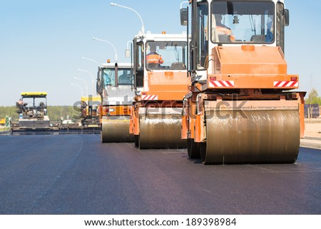 Pneumatic steam road rollers machines compacting fresh asphalt during highway construction works on tracked paver equipment background