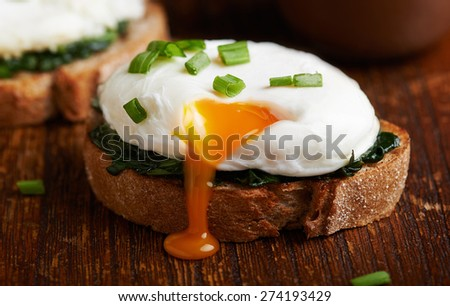 Poached egg on a piece of bread with spinach on the wooden table