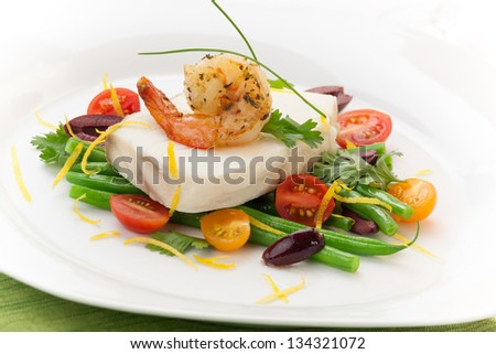 Poached halibut with spicy shrimp, green beans, cherry tomatoes, black olives, and citrus sauce.