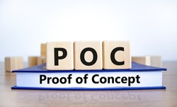 POC, proof of concept symbol. Wooden cubes on book with words POC, proof of concept. Beautiful white background. Business and POC, proof of concept concept, copy space.