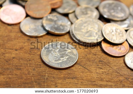 Pocket change, various coins over on old wood surface