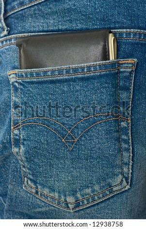 Pocket money. Black leather wallet with dollar bill roll in hip pocket of worn blue jeans close-up.