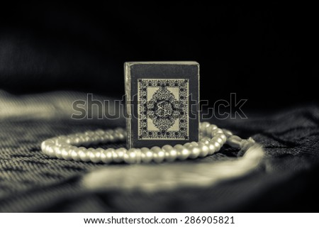Pocket Quran size with white rosary on a praying rag