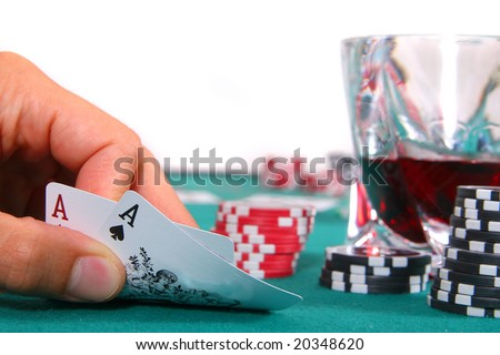 Pocket Rockets A hand is showing two aces on a poker table with a glass of red liquor. Isolated over white.