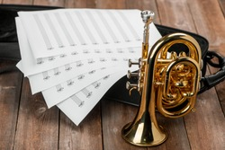 Pocket trumpet, sheet music and case on rustic wooden background. Art and music classes advertisement concept.