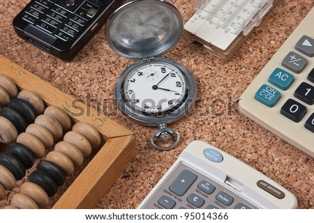 pocket watch, a calculator, a wooden abacus and slide rule on a cork board - stock photo