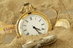 Pocket watch and euro money in the sand - The time value of money concept