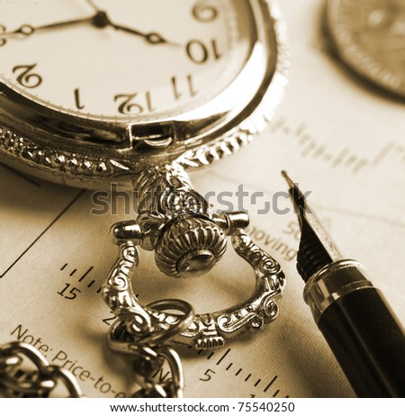 Pocket watch and fountain pen on financial report