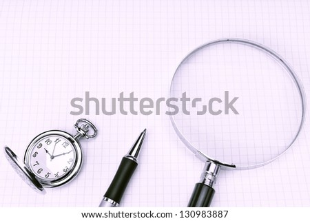Pocket watch, ball pen and magnifier for notebooks, in cold blue tones.
