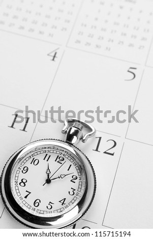 Pocket watch on calendar page