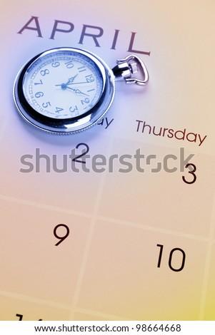 Pocket watch on calendar page