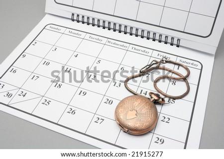 Pocket Watch on Calendar with Grey Background