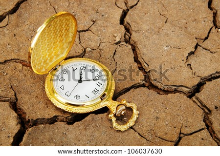 Pocket watch on cracked dry soil
