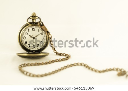 Pocket watch on plain background in sepia tone