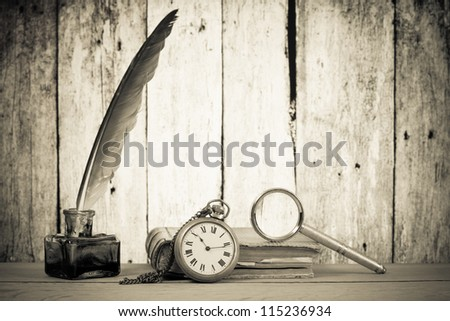 Pocket watch, quill pen and inkwell, book, magnifying glass on the table in front of grunge wooden background