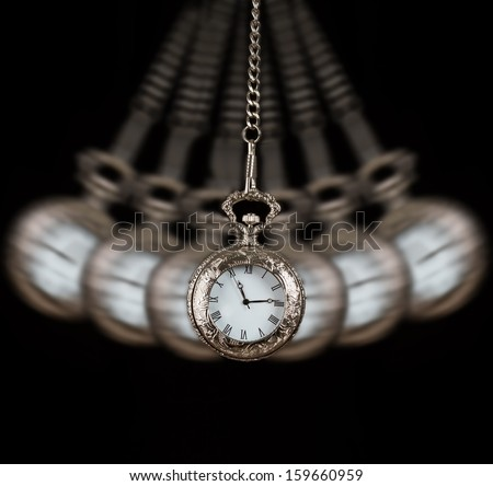 Pocket watch silver swinging on a chain black background to hypnotise