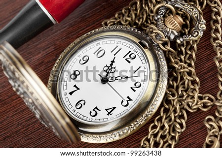 Pocket watch with a lid on a wooden table