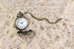 Pocket watch with chain in the sand. Time passing symbol.