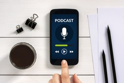 Podcast concept on smart phone screen with office objects on white wooden table. All screen content is designed by me. Flat lay