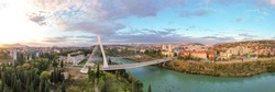 Podgorica, Montenegro: aerial view of Millennium bridge and Moraca river in the morning, at sunrise, under beautiful sky. Cable stayed bridge with green area in the foreground. 180 degree panorama.