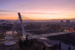 Podgorica Montenegro - city lights and orange and purple sky in the evening, after sunset. Cable-stayed Millennium bridge over river Moraca, at night.