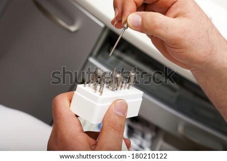 Podiatrist holds a grinder bit in his fingers