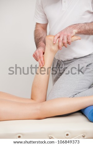 Podiatrist massaging the ankle of a woman in a room