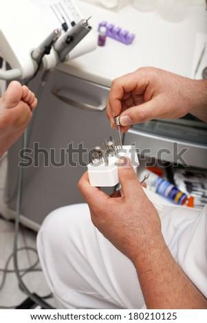 Podiatrist takes a grinder bit out of a box