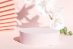 Podium stand pedestal for product presentation, coral pink mockup for branding and packaging. Modern design, pastel color backdrop, flowers and fan. Feminine scene for cosmetic display. Copy space.