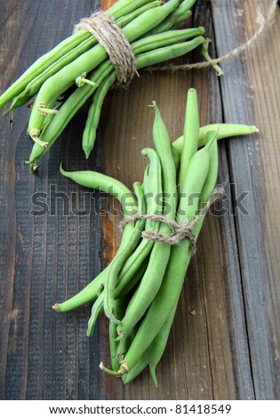 pods of green peas on a wooden table