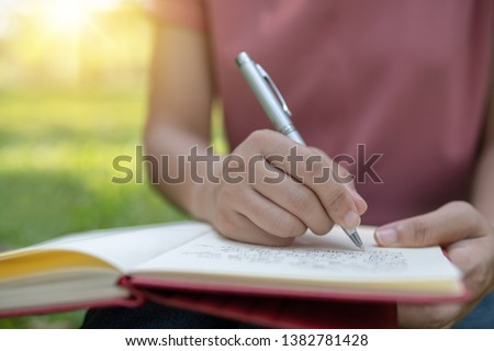 poem, poetry and knowledge education concept,  close up sitting writing on notebook in park Сток-фото ©