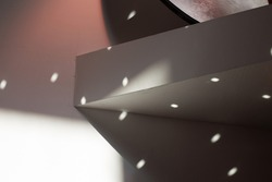 Poetic light hitting on a wall with geometric shapes and lines