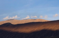 Poetic natural background. View of the Andes mountain range under a blue sky at sunset. The beautiful sunlight and shadow contrast in the mountains.