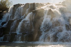 Poetic view of the The Mocona falls. The rocky waterfalls and falling white water with a beautiful sun ray.