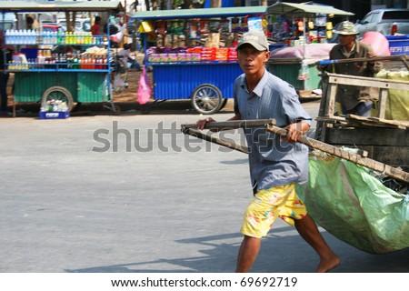 POI PET, THAILAND - JANUARY 19: Man pulls a cart along the road on January 19, 2011 in Poi Pet, Thailand.
