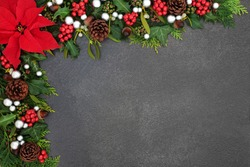 Poinsettia flower background border with silver ball baubles, holly, mistletoe and winter flora on grunge grey background with copy space. Traditional Thanksgiving or Christmas theme.