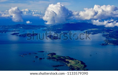 Point of view from the sky of an island, surrounded by calm blue sea, land with green vegetation, and white clouds in the sky. #1133579390